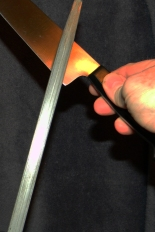 Start  at the Bolster and move the knife edge toward the tip.  Alternate Side to Side